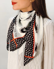 side view of classic woman wearing a luxury, bespoke Elwyn New York silk scarf around her neck with black and white, whimsical, polka dot, bird and stars, storybook print
