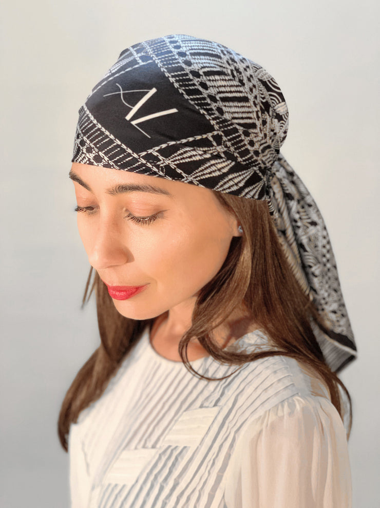 side front view of a classic woman wearing a luxury, bespoke, black and white Elwyn New York silk scarf on her head with vintage modern style graphic needlework and crochet print