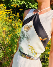 Classic woman in a field of wildflowers, wearing a luxury, bespoke Elwyn New York silk scarf tied around her torso with a vintage style, botanical, floral, butterfly and leopard print