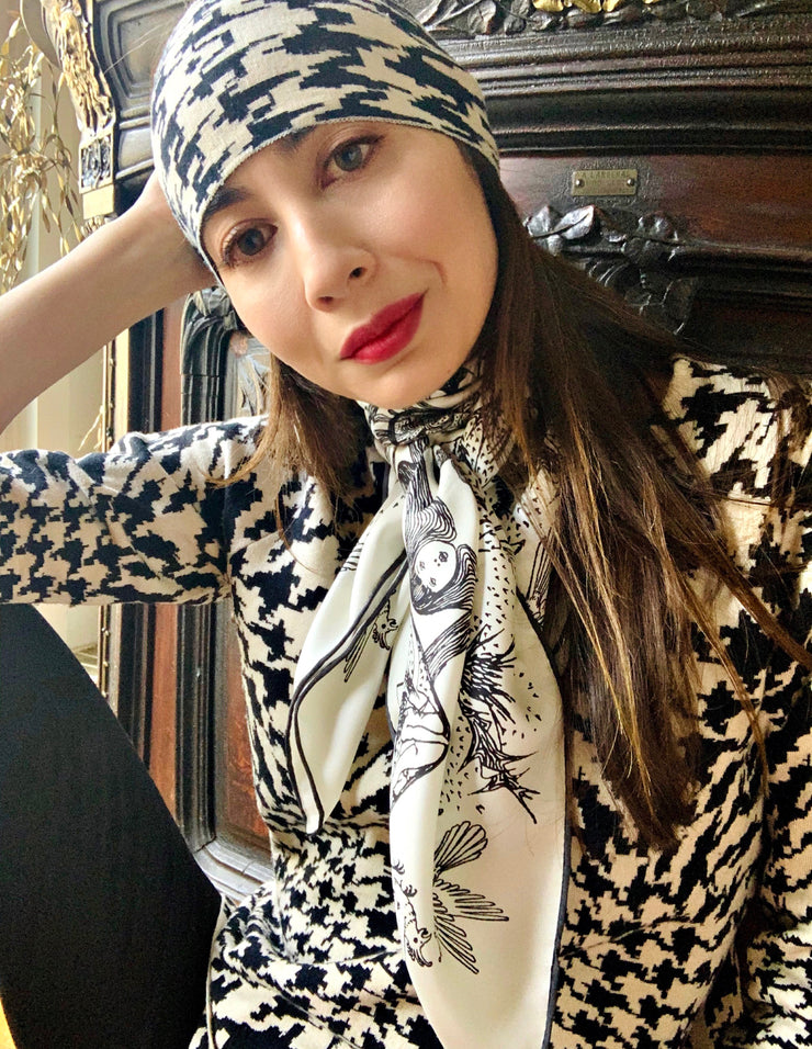 Classic woman wearing a luxury, bespoke Elwyn New York silk scarf around her neck with black and white, art nouveau, whimsical, storybook print