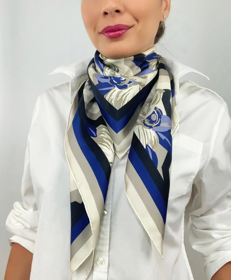 A classic woman wearing a bespoke, luxury elwyn new york scarf looped loosely around her neck. This Denim friendly, zig-zag, art deco floral print feels modern and graphic.