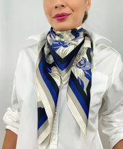 Front view of a classic woman wearing a bespoke, luxury elwyn new york scarf looped around her neck. This Denim friendly, zig-zag, art deco floral print feels modern and graphic.