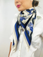 Side view of a classic woman wearing a bespoke, luxury elwyn new york scarf looped around her neck. This Denim friendly, zig-zag, art deco floral print feels modern and graphic.