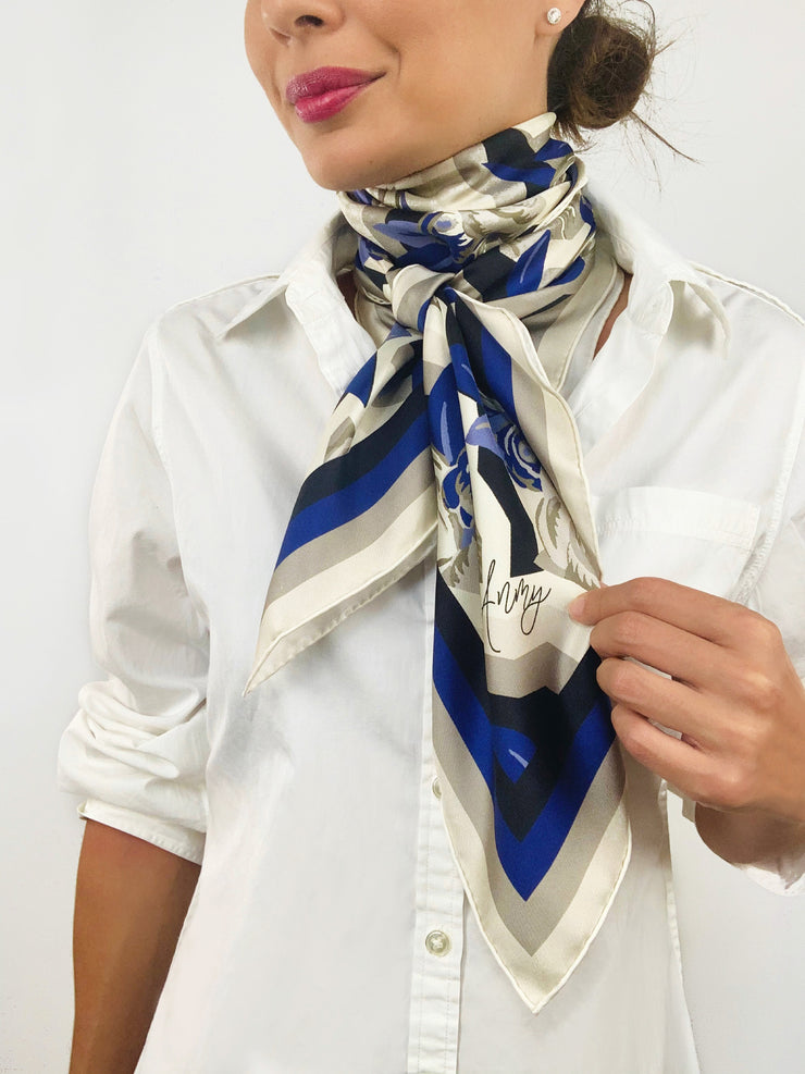 A classic woman wearing a bespoke, luxury elwyn new york scarf tied tightly around her neck. This Denim friendly, zig-zag, art deco floral print feels modern and graphic.