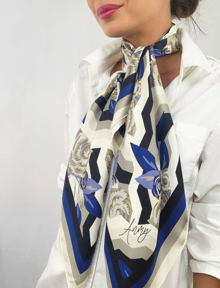 A classic woman wearing a bespoke, luxury elwyn new york scarf draped loose and long around her neck. This Denim friendly, zig-zag, art deco floral print feels modern and graphic.