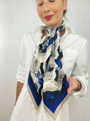 A classic woman wearing a bespoke, luxury elwyn new york scarf tied loose and long around her neck. This Denim friendly, zig-zag, art deco floral print feels modern and graphic. Woman is holding the personalized area of the scarf
