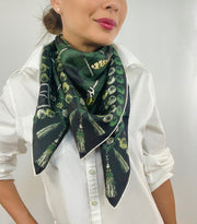 Classic woman wearing bespoke pom-pom and tassel border Elwyn New York scarf looped loosely around her neck. Print has a mix of vintage entomology motifs and playful, victorian ornamental trim. Sophisticated and fun