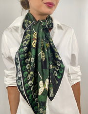 Classic woman wearing bespoke pom-pom and tassel border Elwyn New York scarf loose and long and carelessly around her neck. Print has a mix of vintage entomology motifs and playful, victorian ornamental trim. Sophisticated and fun