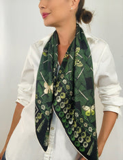 Classic woman wearing bespoke pom-pom and tassel border Elwyn New York scarf loose and long around her neck. Print has a mix of vintage entomology motifs and playful, victorian ornamental trim. Sophisticated and fun