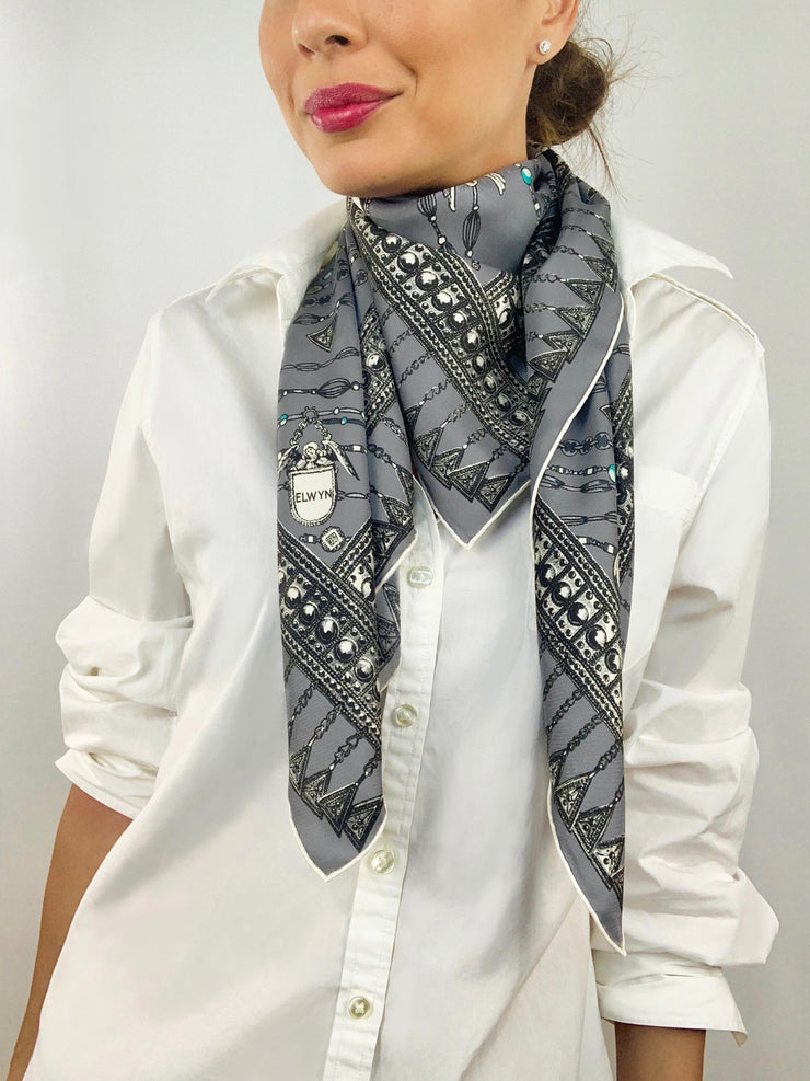Classic woman wearing a bespoke Elwyn New York silk scarf loose and looped around her neck with a vintage chain and beaded sautoir print that has intricate, little charm motifs that are strung together in long flowing chains.