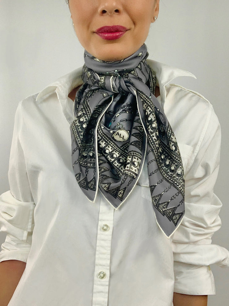 Classic woman wearing a bespoke Elwyn New York silk scarf tied around her neck with a vintage chain and beaded sautoir print that has intricate, little charm motifs that are strung together in long flowing chains. Personalized detail can be seen on printed charm