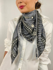 Classic woman wearing a bespoke Elwyn New York silk scarf loose and looped around her neck with a vintage chain and beaded sautoir print that has intricate, little charm motifs that are strung together in long flowing chains. Personalized detail can be seen on printed charm