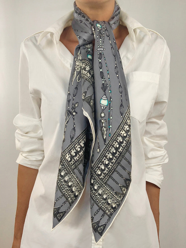 Classic woman wearing a bespoke Elwyn New York silk scarf tied tight and long around her neck with a vintage chain and beaded sautoir print that has intricate, little charm motifs that are strung together in long flowing chains.