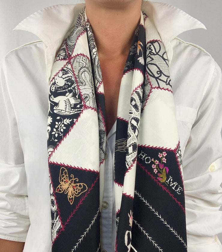 Classic woman wearing bespoke, luxury Elwyn New York silk scarf draped long and loose around her neck. This geometric crazy quilt print is a vintage-modern depiction of the year 2020 filled with digital embroidery and lace of years past. One can see the word HOME depicted in this photo