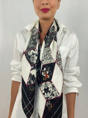 Classic woman wearing bespoke, luxury Elwyn New York silk scarf draped long and loose around her neck. This geometric crazy quilt print is a vintage-modern depiction of the year 2020 filled with digital embroidery and lace of years past. One can see the word GROW depicted in this photo