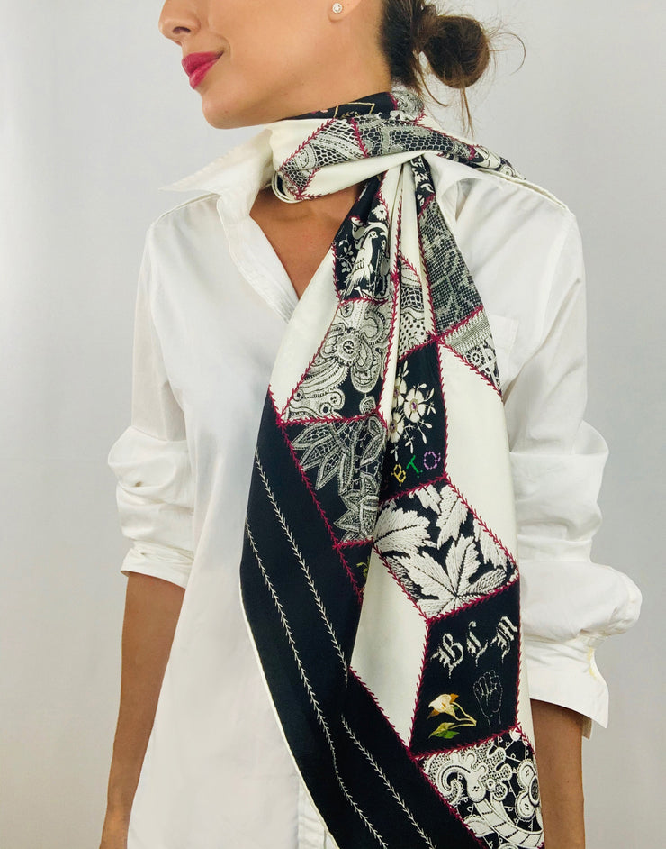 Classic woman wearing bespoke, luxury Elwyn New York silk scarf draped long and loose around her neck. This geometric crazy quilt print is a vintage-modern depiction of the year 2020 filled with digital embroidery and lace of years past.  One can see the words LGBTQ and BLM depicted in this photo