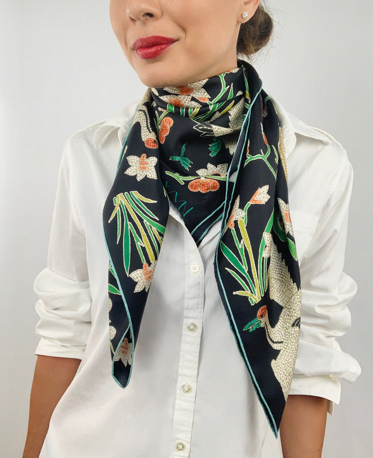 Classic woman wearing bespoke Elwyn New York Scarf draped in a loop around her neck with a botanical crane print is collaged together from antique glass and pearl, beaded embroideries of yesteryear.