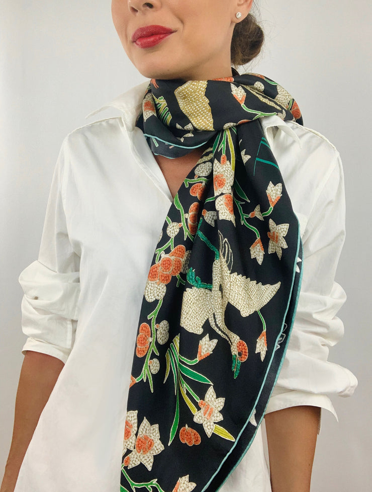 Classic woman wearing bespoke Elwyn New York Scarf draped loose and long around her neck with a botanical crane print is collaged together from antique glass and pearl, beaded embroideries of yesteryear.