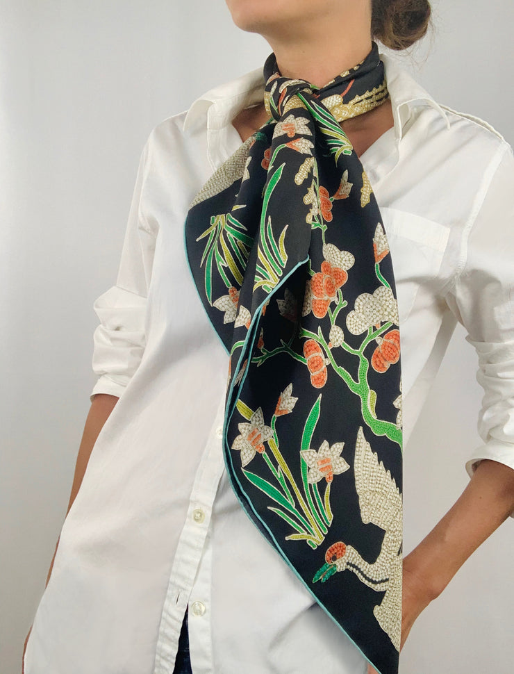 Classic woman wearing bespoke Elwyn New York Scarf tied long around her neck with a botanical crane print is collaged together from antique glass and pearl, beaded embroideries of yesteryear.