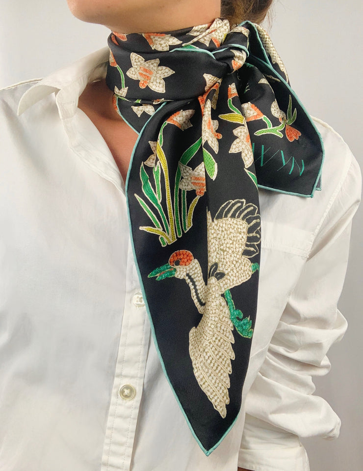 Classic woman wearing bespoke Elwyn New York Scarf tied  around her neck with a botanical crane print is collaged together from antique glass and pearl, beaded embroideries of yesteryear.