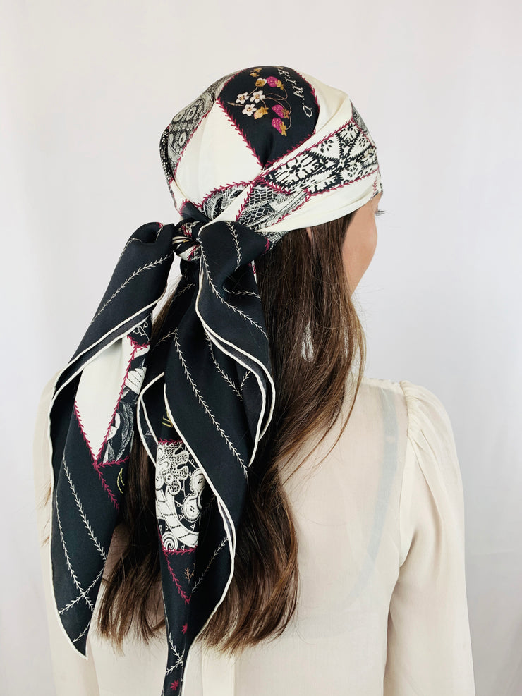 Side back view of a Classic woman wearing bespoke, luxury Elwyn New York silk scarf around her head . This geometric crazy quilt print is a vintage-modern depiction of the year 2020 filled with digital embroidery and lace of years past. One can see the word KIND depicted in this photo