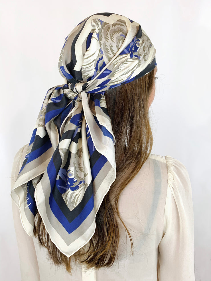 A classic woman wearing a bespoke, luxury elwyn new york scarf around her head. This Denim friendly, zig-zag, art deco floral print feels modern and graphic.