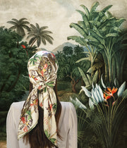 classic female standing in a fantastical, illustrated lush frond Jungle in Vietnam wearing luxury, bespoke Elwyn New York silk scarf on her head with vintage tropical, floral, bamboo, leopard wall paper print