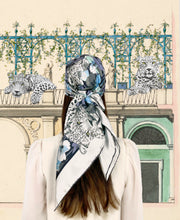 classic female traveler standing in front of a vintage garden Illustration, wearing a luxury, bespoke Elwyn New York silk scarf on her head with vintage style print of floral field and modern lazing leopards