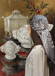 Classic Female standing in front of a intricate illustration of antique carved porcelain, wearing a luxury, bespoke, black and white Elwyn New York silk scarf on her head with vintage modern style graphic needlework and crochet print