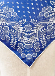 Closeup photo of a bespoke Elwyn New York Scarf with an ornate, blue and white, vintage-pastoral bandana design. Classic, feminine, and romantic with an example pf customer's initials on it