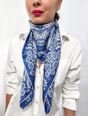 Woman wearing a bespoke Elwyn New York Scarf around her neck with an ornate, blue and white, vintage-pastoral bandana design. Classic, feminine, and romantic