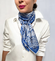 Woman wearing a bespoke Elwyn New York Scarf wrapped around her neck with an ornate, blue and white, vintage-pastoral bandana design. Classic, feminine, and romantic