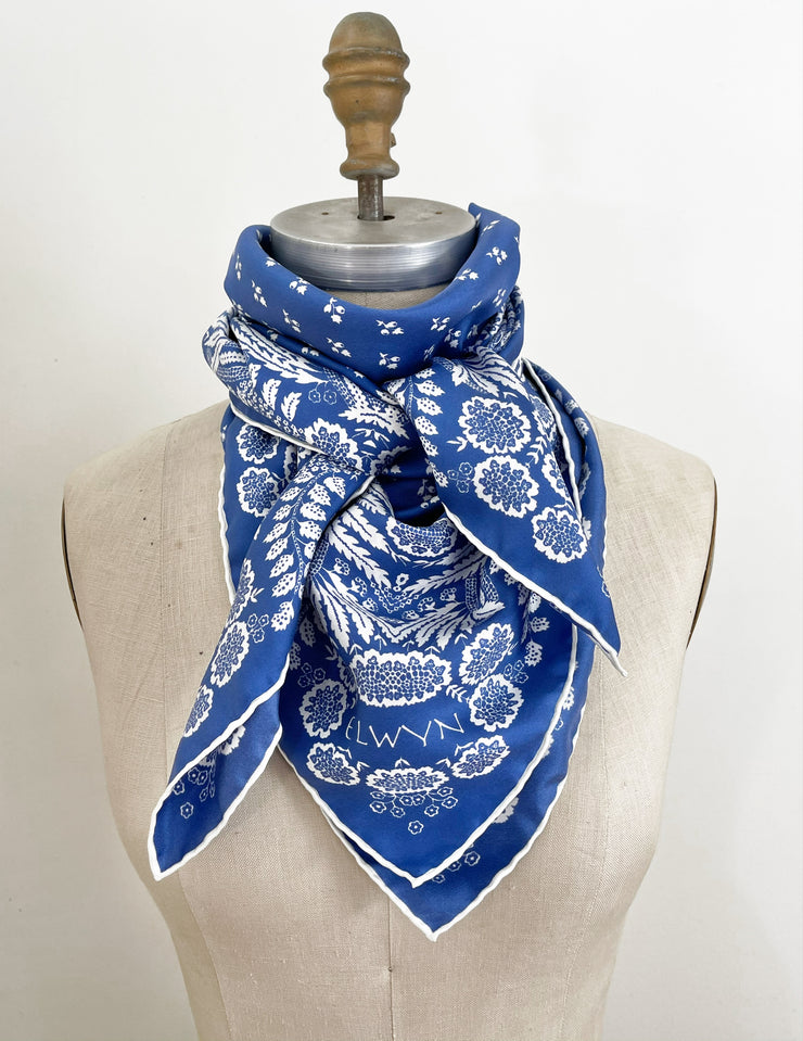 a bespoke Elwyn New York Scarf wrapped around the neck of a form with an ornate, blue and white, vintage-pastoral bandana design. Classic, feminine, and romantic