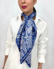 Woman wearing a bespoke Elwyn New York Scarf draped knotted at the neck with an ornate, blue and white, vintage-pastoral bandana design. Classic, feminine, and romantic