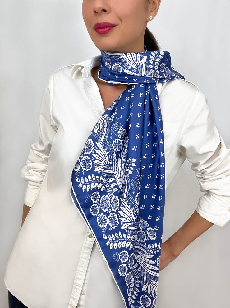 Woman wearing a bespoke Elwyn New York Scarf draped around her neck on one side with an ornate, blue and white, vintage-pastoral bandana design. Classic, feminine, and romantic