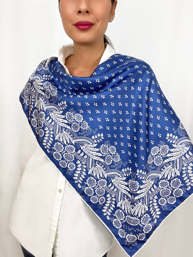 Woman wearing a bespoke Elwyn New York Scarf draped draped on one shoulder with an ornate, blue and white, vintage-pastoral bandana design. Classic, feminine, and romantic