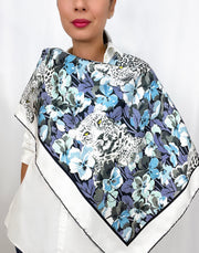 Classic woman wearing a luxury, bespoke Elwyn New York silk scarf draped on her front side, with vintage style print of floral field and modern lazing leopards