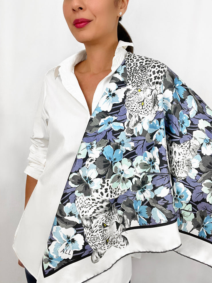 Classic woman wearing a luxury, bespoke Elwyn New York silk scarf draped on one shoulder, with vintage style print of floral field and modern lazing leopards