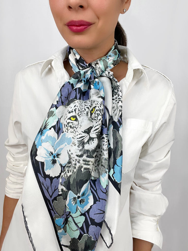 Classic woman wearing a luxury, bespoke Elwyn New York silk scarf tied long and loose around her neck with vintage style print of floral field and modern lazing leopards