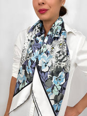 Classic woman wearing a luxury, bespoke Elwyn New York silk scarf draped around her neck with vintage style print of floral field and modern lazing leopards