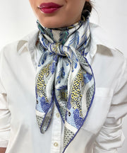 Woman wearing a bespoke Elwyn New York silk scarf around her neck, with a delightful design of swirling feathers, surrounded by creeping jaguars and parrots in the graphic border.