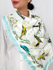 a classic woman wearing a personalized, bespoke Elwyn New York silk scarf draped around on her shoulders with a Charming blue and yellow warbler birds, flying and perched amidst delicate wild flowers. Inspired by nature found in the North East.