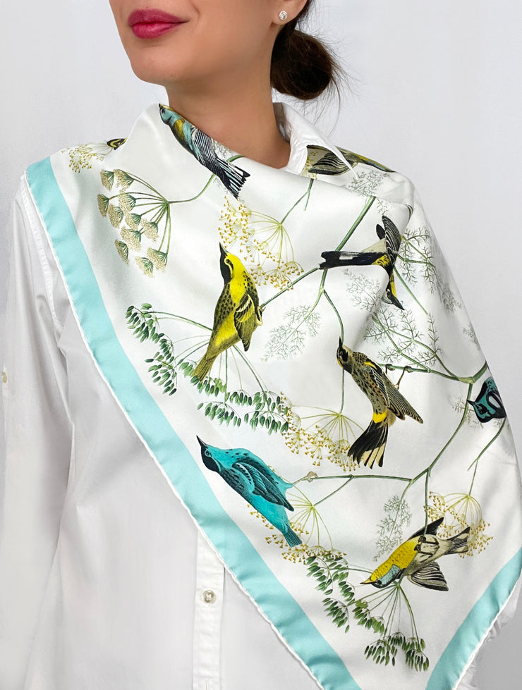 a classic woman wearing a bespoke Elwyn New York silk scarf draped around on her shoulders with a Charming blue and yellow warbler birds, flying and perched amidst delicate wild flowers. Inspired by nature found in the North East.