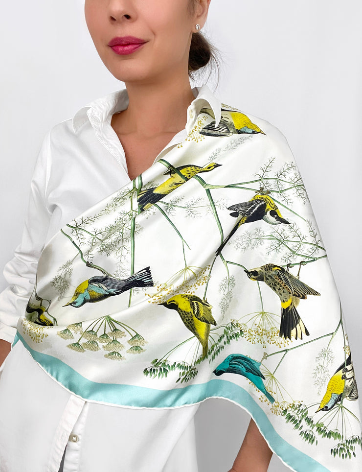 a classic woman wearing a personalized, bespoke Elwyn New York silk scarf draped around one shoulder with a Charming blue and yellow warbler birds, flying and perched amidst delicate wild flowers. Inspired by nature found in the North East.
