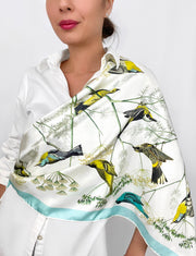 a classic woman wearing a bespoke Elwyn New York silk scarf draped around one shoulder with a Charming blue and yellow warbler birds, flying and perched amidst delicate wild flowers. Inspired by nature found in the North East.