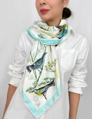 a classic woman wearing a bespoke Elwyn New York silk scarf draped around her neck on one side with a Charming blue and yellow warbler birds, flying and perched amidst delicate wild flowers. Inspired by nature found in the North East.