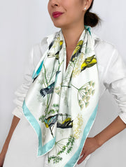 a classic woman wearing a bespoke Elwyn New York silk scarf draped around her neck with a Charming blue and yellow warbler birds, flying and perched amidst delicate wild flowers. Inspired by nature found in the North East.