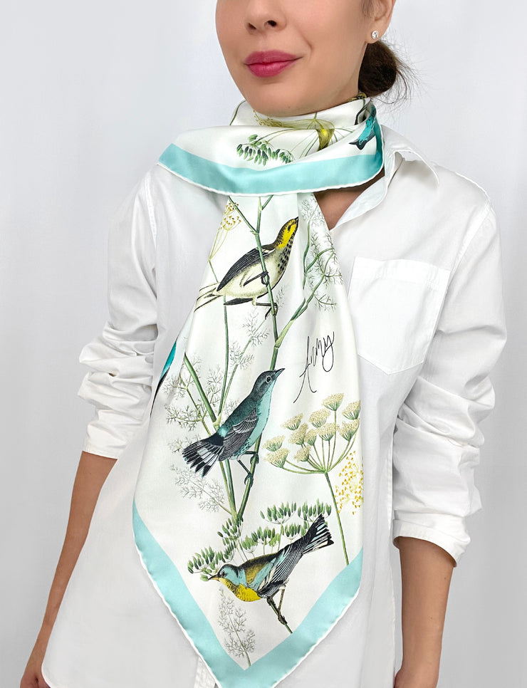 a classic woman wearing a personalized bespoke Elwyn New York silk scarf draped around her neck on one side with a Charming blue and yellow warbler birds, flying and perched amidst delicate wild flowers. Inspired by nature found in the North East.