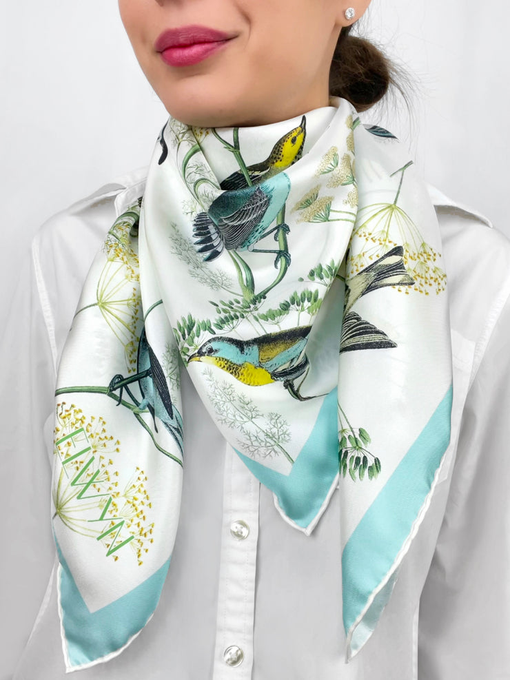 a classic woman wearing a personalized bespoke Elwyn New York silk scarf around her neck with a Charming blue and yellow warbler birds, flying and perched amidst delicate wild flowers. Inspired by nature found in the North East.