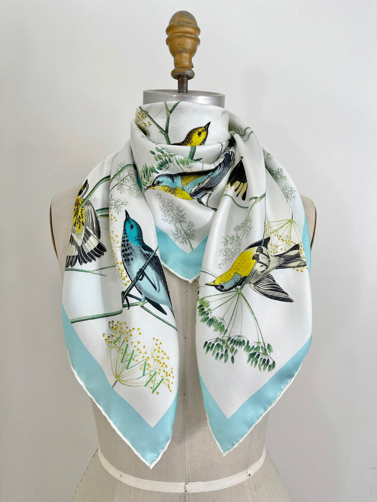 a personalized bespoke Elwyn New York silk scarf around the neck of a form with a Charming blue and yellow warbler birds, flying and perched amidst delicate wild flowers. Inspired by nature found in the North East.